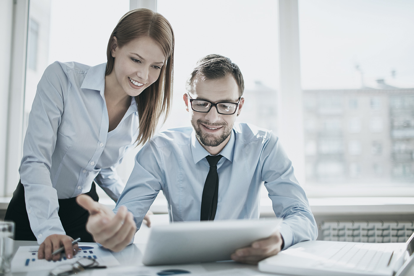 Man and woman smiling whilst reading a document